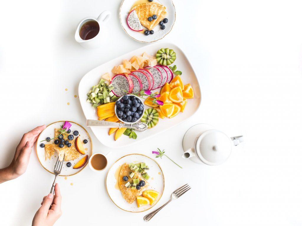 Früchte und ein gesundes Frühstück auf hellem Untergrund für den optimalen Start in den Tag – Foto: Brooke Lark / Unsplash