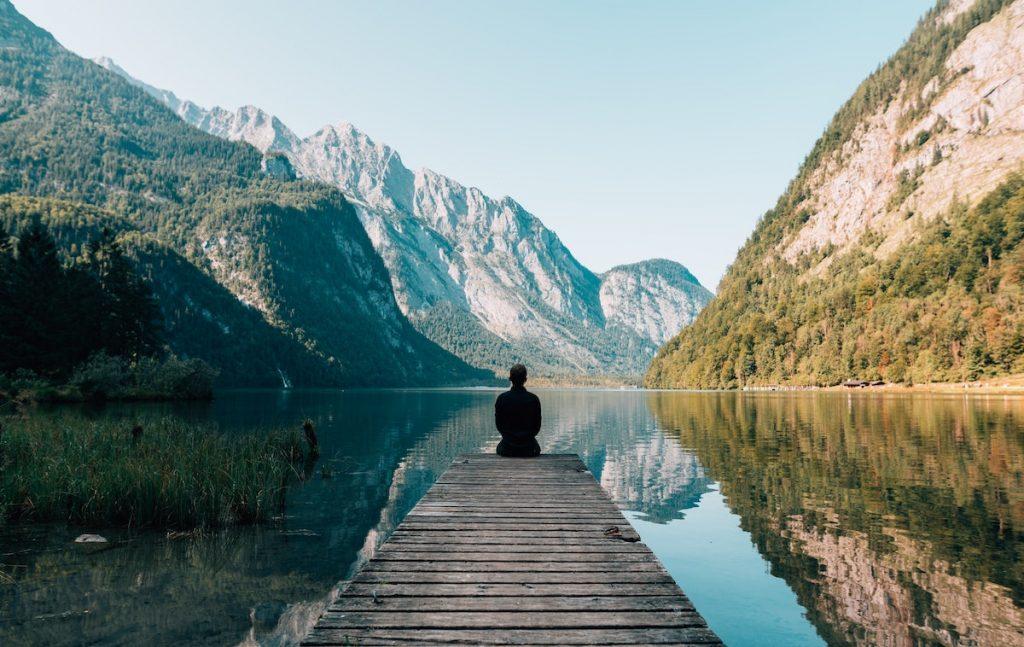 Mensch auf einem Steg am Wasser, im Hintergrund Berge